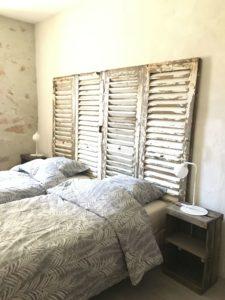 gite avec tête de lit relookée avec des anciennes persiennes